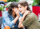 Two female friends sitting in a sidewalk cafe. They are whispering and gossiping.